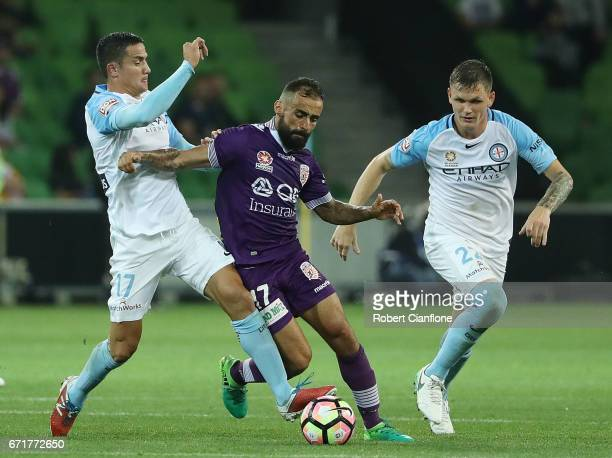 Diego Castro of Perth Glory is challenged by Tim Cahill and Michael Jakobsen of Melbourne City during the ALeague Elimination Final match between...