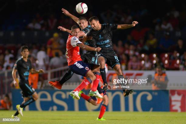 Diego Chavez of Veracruz goes for a header with Javier Guemez and Jonathan Bornstein of Queretaro during the fifth round match between Veracruz and...