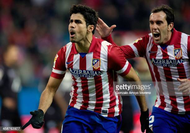 Diego Costa of Atletico de Madrid celebrates scoring their second goal with teammate Diego Godin during the La Liga match between Club Atletico de...