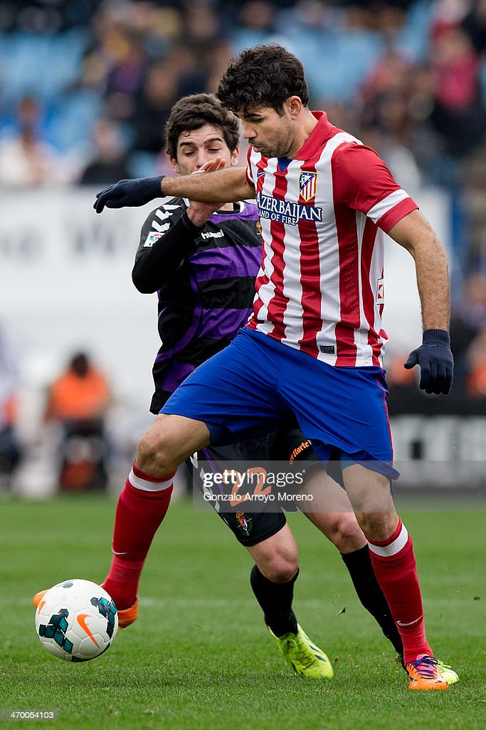 Diego Costa of Atletico de Madrid competes for the ball ahead Victor Perez of Real Valladolid CF during the La Liga match between Club Atletico de Madrid and Real Valladolid CF at Vicente Calderon Stadium on February 15, 2014 in Madrid, Spain.