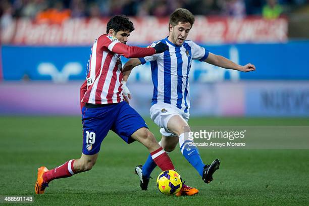 Diego Costa of Atletico de Madrid competes for the ball with Jon Gaztanaga of Real Sociedad during the La Liga match between Club Atletico de Madrid...