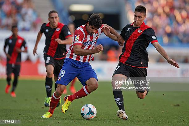 Diego Costa of Atletico de Madrid competes for the ball with Leonel Galeano of Rayo Vallecano de Madrid during the La Liga match between Club...