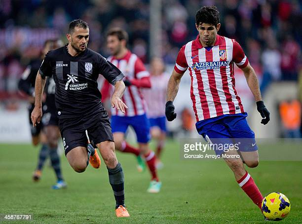 Diego Costa of Atletico de Madrid competes for the ball with Loukas Vyntra of Levante UD during the La Liga match between Club Atletico de Madrid and...