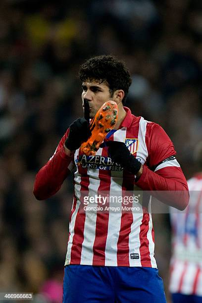 Diego Costa of Atletico de Madrid presses his finger to his lips towards some Real Madrid players as he holds his shoe during the Copa del Rey...