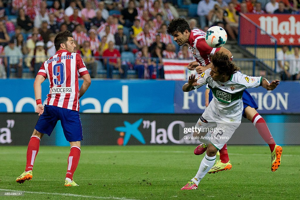 Diego Costa of Atletico de Madrid wins the header before Damian Suarez of Elche FC as <a gi-track='captionPersonalityLinkClicked' href=/galleries/search?phrase=David+Villa&family=editorial&specificpeople=467566 ng-click='$event.stopPropagation()'>David Villa</a> (L) looks them during the La Liga match between Club Atletico de Madrid and Elche FC at Vicente Calderon Stadium on April 18, 2014 in Madrid, Spain.