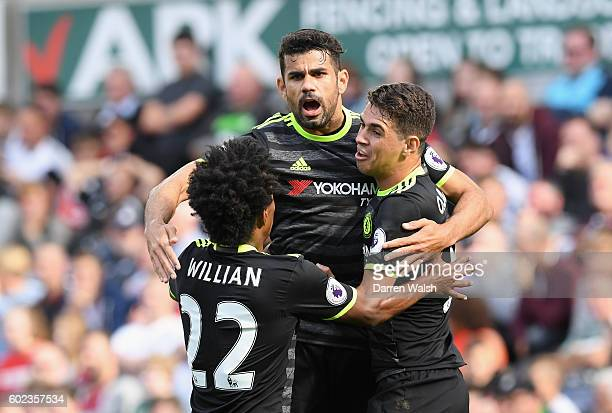 Diego Costa of Chelsea celebrates with team mates Willian and Oscar of Chelsea as he scores their first goal during the Premier League match between...