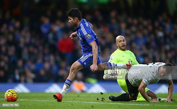 Diego Costa of Chelsea rounds Tim Howard and Phil Jagielka of Everton to score his team's first goal during the Barclays Premier League match between...