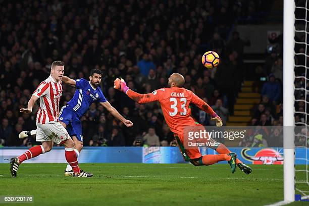 Diego Costa of Chelsea scores his side's fourth goal past Lee Grant of Stoke City during the Premier League match between Chelsea and Stoke City at...