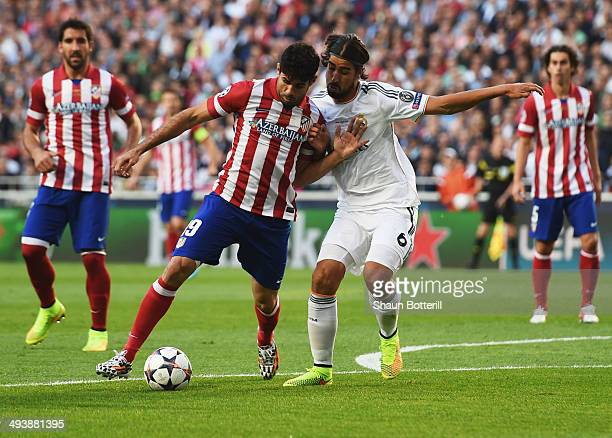 Diego Costa of Club Atletico de Madrid holds off Sami Khedira of Real Madrid during the UEFA Champions League Final between Real Madrid and Atletico...