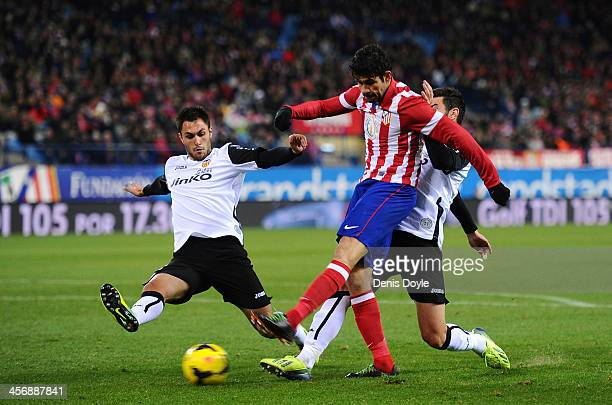 Diego Costa of Club Atletico de Madrid shoots past Victor Ruiz of Valencia CF to score Atletico's opening goal during the La Liga match between Club...