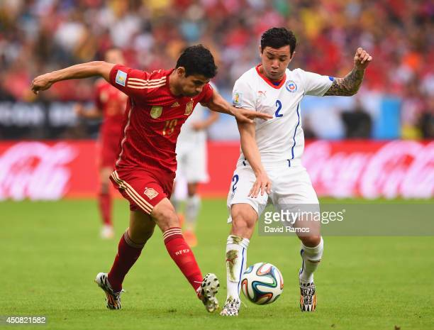 Diego Costa of Spain and Eugenio Mena of Chile compete for the ball during the 2014 FIFA World Cup Brazil Group B match between Spain and Chile at...