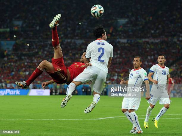 Diego Costa of Spain attempts an overhead kick under pressure from Eugenio Mena of Chile during the 2014 FIFA World Cup Brazil Group B match between...