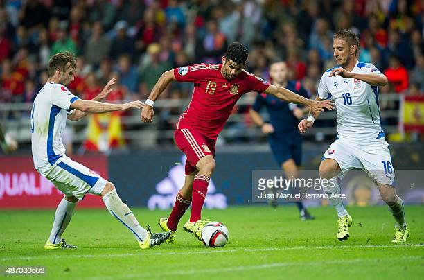 Diego Costa of Spain duels for the ball with Norbert Gyomber and Kornel Salata of Slovakia during the Spain v Slovakia EURO 2016 Qualifier at Carlos...