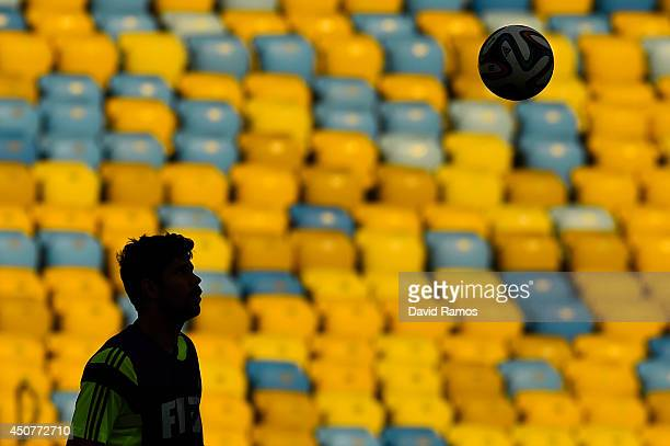 Diego Costa of Spain heads the ball during a Spain training session ahead of their 2014 FIFA World Cup Group B match against Chile at Maracana on...