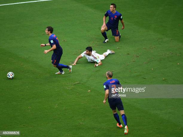 Diego Costa of Spain lies on the field after being fould by Gerard Pique of Spain and awarded a penalty kick in the first half during the 2014 FIFA...