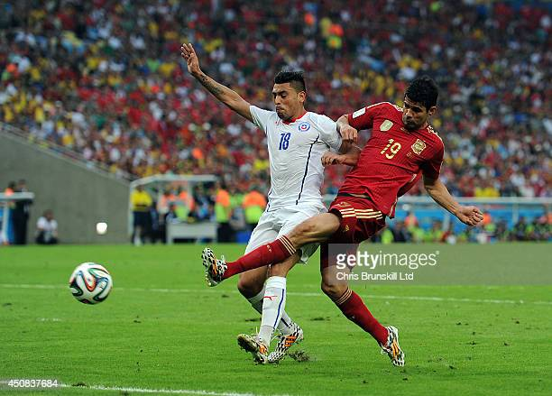 Diego Costa of Spain shoots at the goal under pressure from Gonzalo Jara of Chile during the 2014 FIFA World Cup Brazil Group B match between Spain...