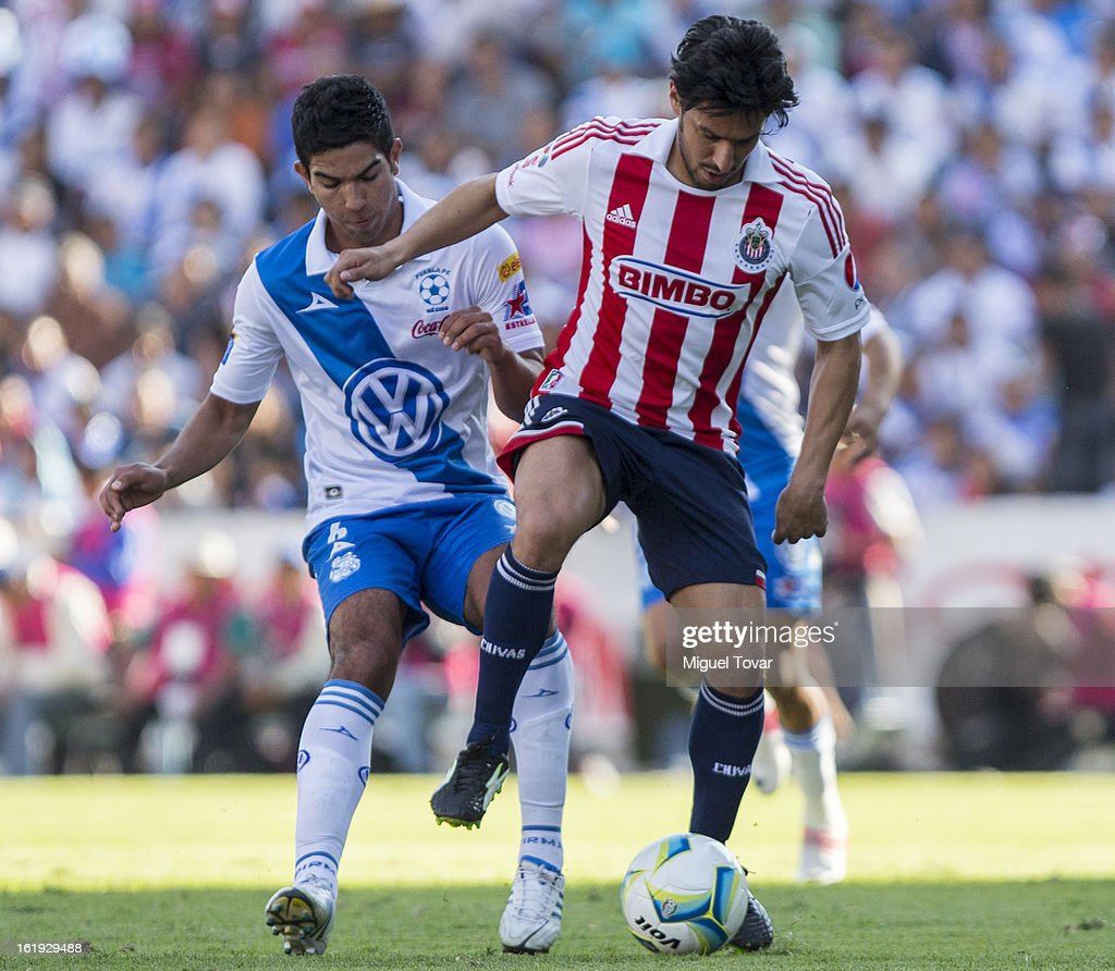 Diego de Buen (L) of Puebla fights for the ball with Rafael Marquez (R) of Chivas during a match between Puebla and Chivas as part of the Clausura 2013 at Cuauhtemoc Stadium on February 17, 2013 in Puebla, Mexico.
