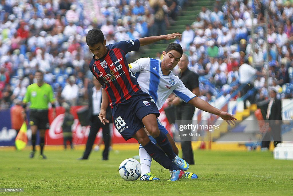 Diego de Buen (R) of Puebla struggles for the ball with Alberto Garcia (L) of Atlante during a match between Puebla and Atlas as part of the Apertura 2013 Liga Bancomer MX at Cuahtemoc Stadium on september 01, 2013 in Puebla, Mexico.