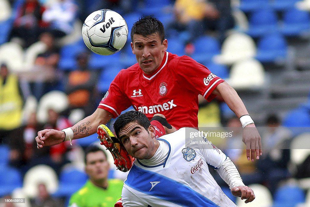 <a gi-track='captionPersonalityLinkClicked' href=/galleries/search?phrase=Diego+de+Buen&family=editorial&specificpeople=7624335 ng-click='$event.stopPropagation()'>Diego de Buen</a> (L) of Puebla struggles for the ball with <a gi-track='captionPersonalityLinkClicked' href=/galleries/search?phrase=Edgar+Benitez&family=editorial&specificpeople=3433635 ng-click='$event.stopPropagation()'>Edgar Benitez</a> (R) of Toluca during a match as part of Apertura 2013 Liga MX at Cuauhtemoc Stadium on September 14, 2013 in Puebla, Mexico.