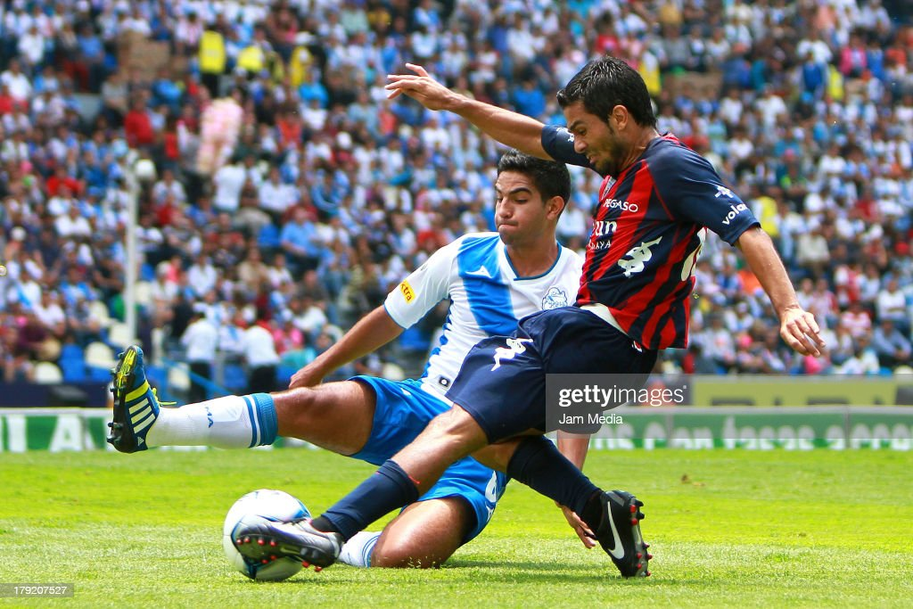 Diego de Buen (L) of Puebla struggles for the ball with Walter Erviti (R) of Atlante during a match between Puebla and Atlas as part of the Apertura 2013 Liga Bancomer MX at Cuahtemoc Stadium on september 01, 2013 in Puebla, Mexico.