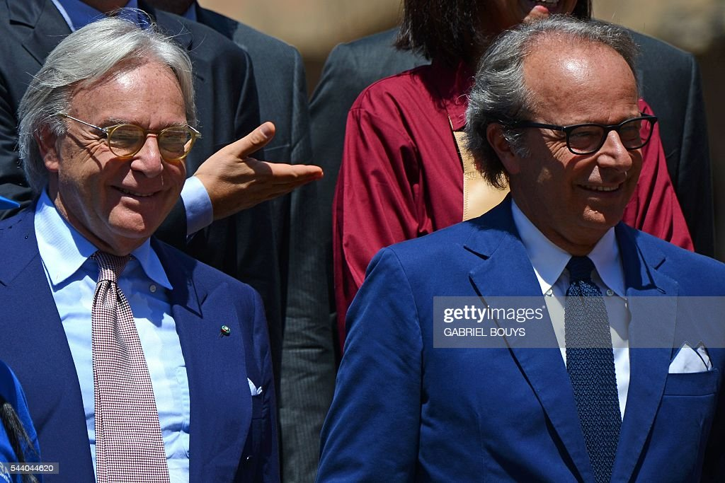 Diego della Valle (L), CEO of luxury shoe brand Tod's, jokes with his brother Andrea Della Valle during a press conference on July 1, 2016 in Rome to announce the end of the restoration of the façade of the Colosseum financed by top luxury brands. / AFP / GABRIEL