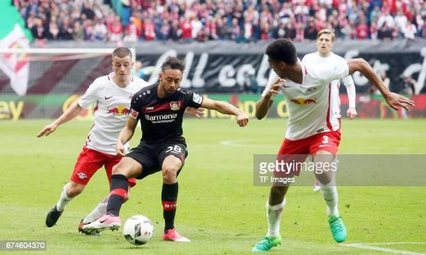 Diego Demme of Leipzig and Karim Bellarabi of Leverkusen and Bernardo of Leipzig battle for the ball during the Bundesliga match between RB Leipzig...