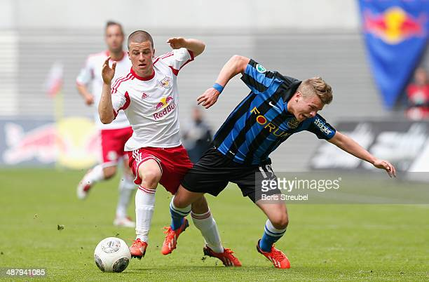 Diego Demme of Leipzig is challenged by Andre Mandt of Saarbruecken during the third league match between RB Leipzig and 1 FC Saarbruecken at Red...