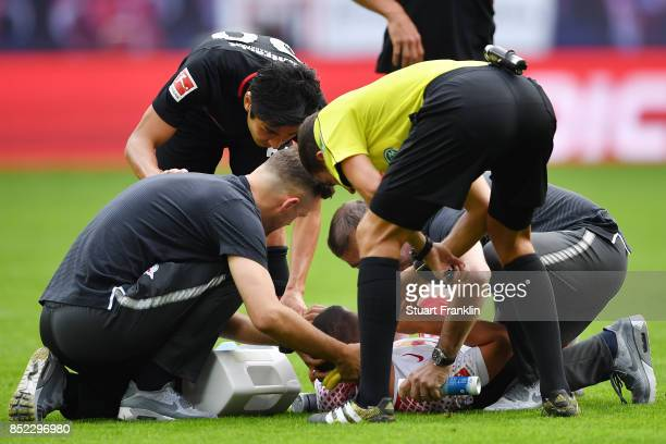 Diego Demme of Leipzig lies on the pitch injured and is looked after by medics and referee Benjamin Brand during the Bundesliga match between RB...