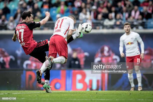 Diego Demme of Leipzig scores his team's fourth goal against Nicolas Hoefler of Freiburg during the Bundesliga match between RB Leipzig and SC...