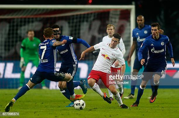 Diego Demme of RB Leipzig is challenged by players of FC Schalke 04 during the Bundesliga match between RB Leipzig and FC Schalke 04 at Red Bull...