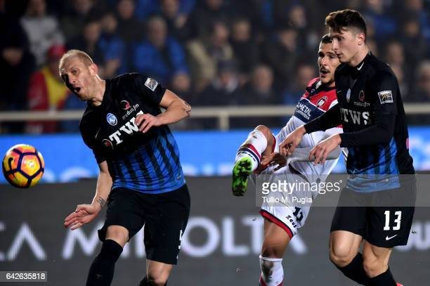 Diego Falcinelli of Crotone kicks the ball as Andrea Masiello and Mattia Caldara of Atalanta tackle during the Serie A match between Atalanta BC and...