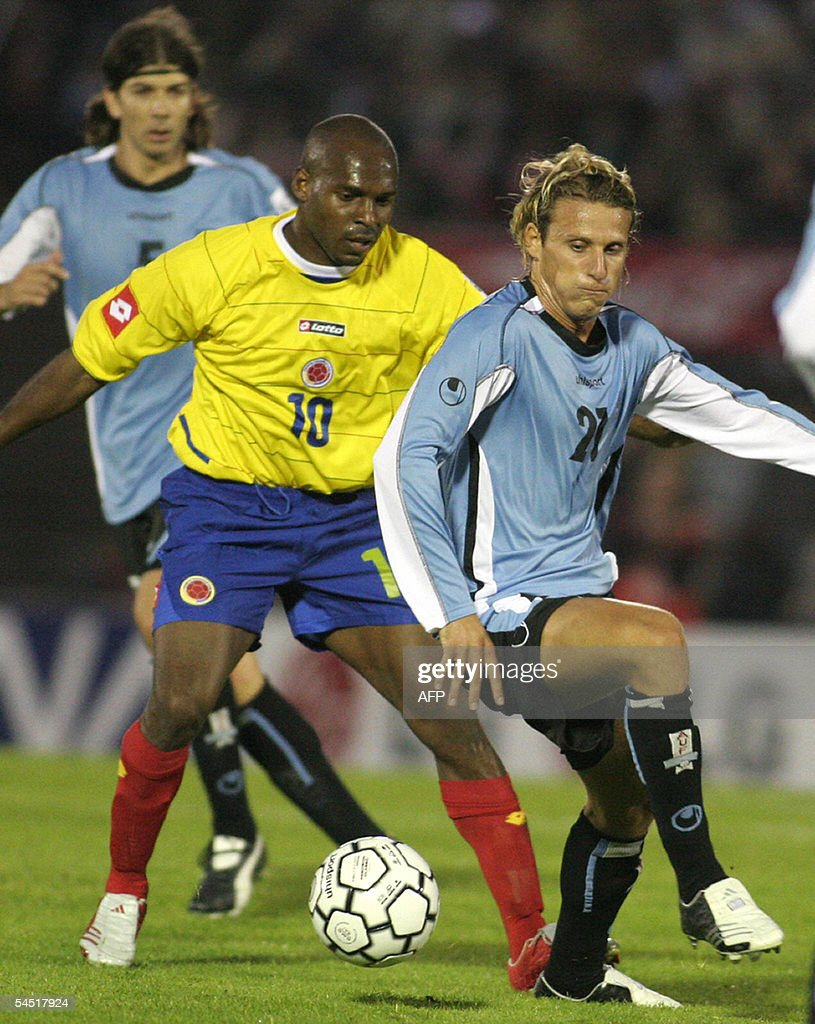 Diego Forlan R from Uruguay vies with
