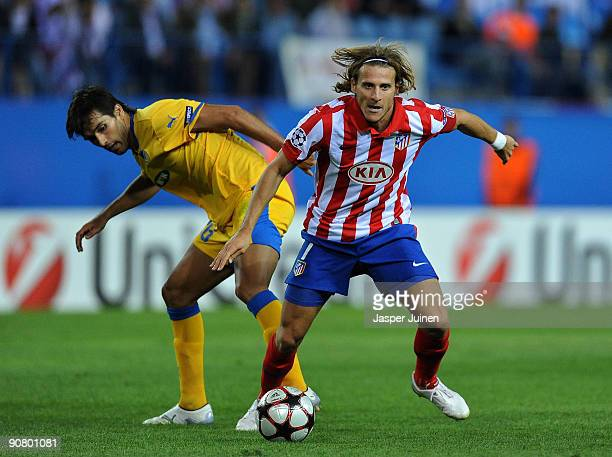 Diego Forlan of Atletico de Madrid duels for the ball with Nuno Morais of APOEL FC during the Champions League group D match between Atletico Madrid...