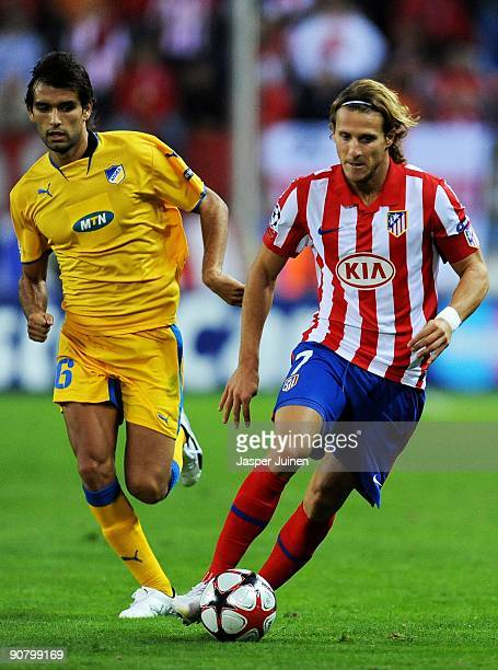 Diego Forlan of Atletico de Madrid runs with the ball ahead of Nuno Morais of APOEL FC during the Champions League group D match between Atletico...