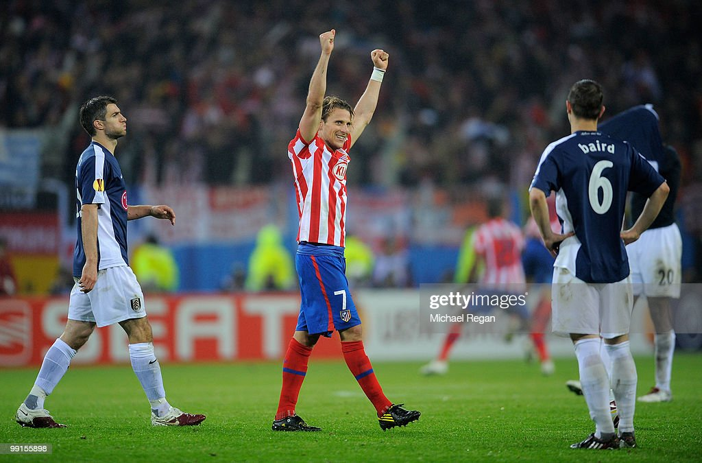 Diego Forlan (C) of Atletico Madrid celebrates his victory while Chris Baird of Fulham looks dejected after the UEFA Europa League final match between Atletico Madrid and Fulham at HSH Nordbank Arena on May 11, 2010 in Hamburg, Germany.