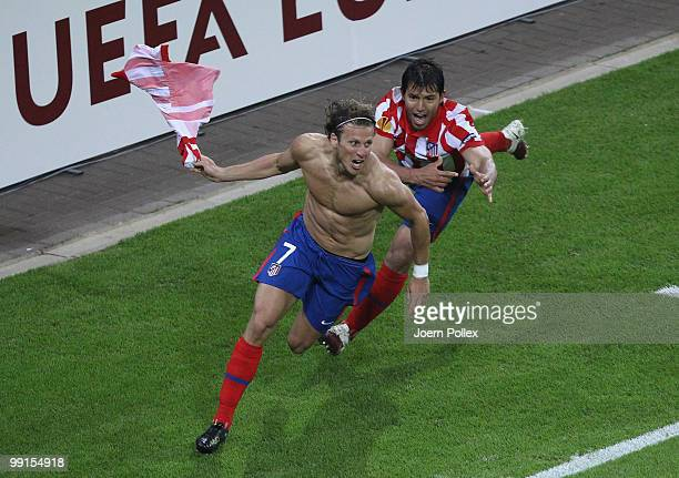 Diego Forlan of Atletico Madrid celebrates with team mate Sergio Aguero after scoring his team's second and winning goal in extra time during the...
