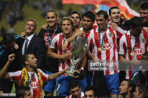 Diego Forlan of Atletico Madrid hugs the Super Cup after his sides 20 victory during the UEFA Super Cup match between Inter Milan and Atletico Madrid...