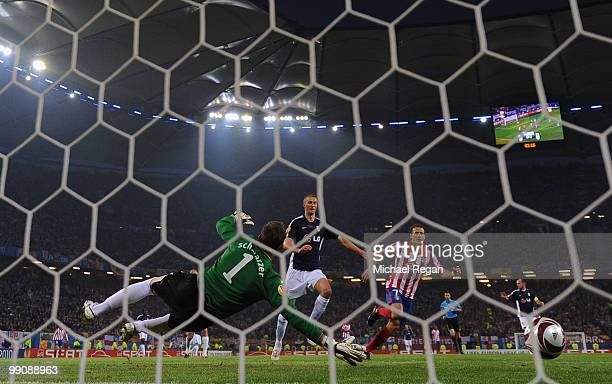Diego Forlan of Atletico Madrid scores the opening goal against goalkeeper Mark Schwarzer of Fulham during the UEFA Europa League final match between...