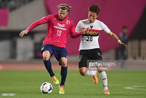 Diego Forlan of Cerezo Osaka and Son Junho of Pohang Steelers compete for the ball during the AFC Champions League Group E match between Cerezo Osaka...