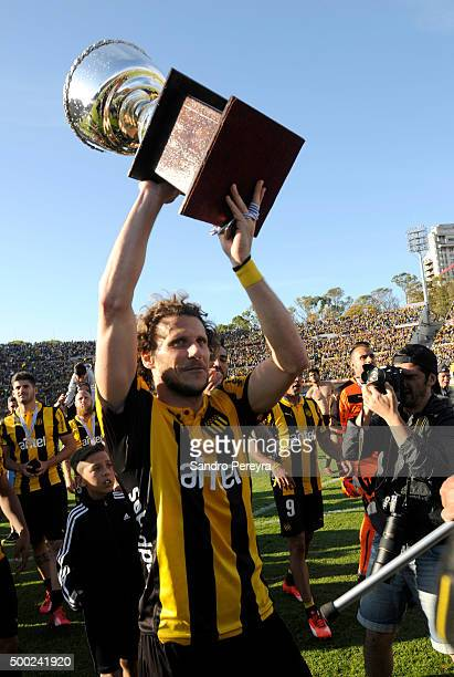 Diego Forlan of Pen–arol raises the trophy after winning a final match between Penarol and Juventud as part of Torneo Apertura 2015 at Centenario...