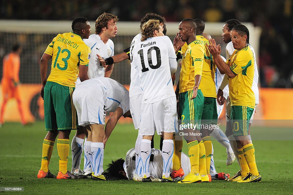Diego Forlan of Uruguay argues with Siboniso Gaxa of South Africa as Jorge Fucile lies on the ground injured during the 2010 FIFA World Cup South...