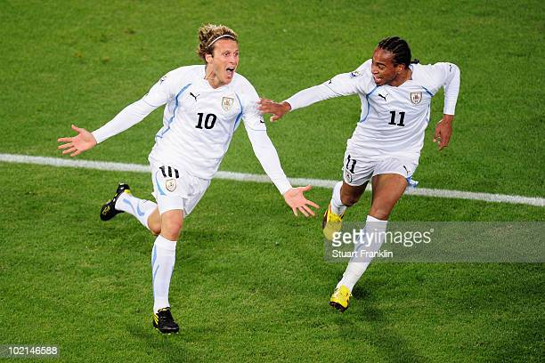 Diego Forlan of Uruguay celebrates after scoring the opening goal with team mate Alvaro Pereira during the 2010 FIFA World Cup South Africa Group A...