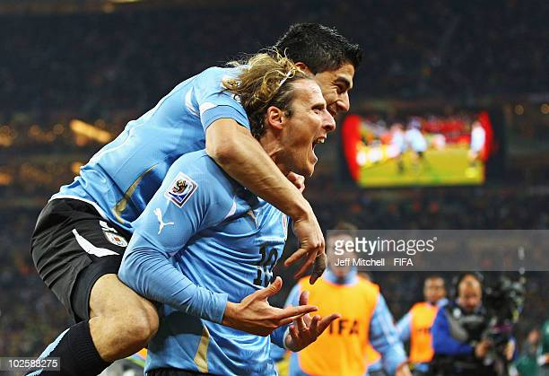 Diego Forlan of Uruguay celebrates scoring his side's first goal from a free kick with team mate Luis Suarez during the 2010 FIFA World Cup South...