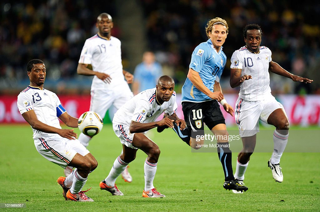 <a gi-track='captionPersonalityLinkClicked' href=/galleries/search?phrase=Diego+Forlan&family=editorial&specificpeople=171096 ng-click='$event.stopPropagation()'>Diego Forlan</a> of Uruguay comes under pressure from <a gi-track='captionPersonalityLinkClicked' href=/galleries/search?phrase=Patrice+Evra&family=editorial&specificpeople=714865 ng-click='$event.stopPropagation()'>Patrice Evra</a> (L), Eric Abidal (C) and <a gi-track='captionPersonalityLinkClicked' href=/galleries/search?phrase=Sidney+Govou&family=editorial&specificpeople=242983 ng-click='$event.stopPropagation()'>Sidney Govou</a> (R) of France during the 2010 FIFA World Cup South Africa Group A match between Uruguay and France at Green Point Stadium on June 11, 2010 in Cape Town, South Africa.