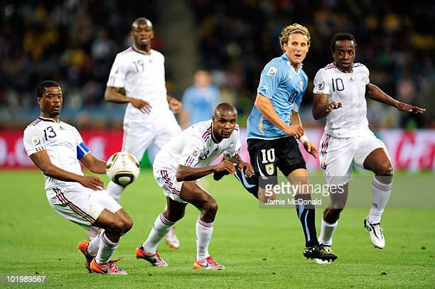 Diego Forlan of Uruguay comes under pressure from Patrice Evra Eric Abidal and Sidney Govou of France during the 2010 FIFA World Cup South Africa...