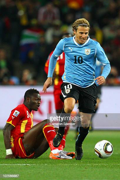 Diego Forlan of Uruguay evades the challenge of Sulley Muntari of Ghana during the 2010 FIFA World Cup South Africa Quarter Final match between...