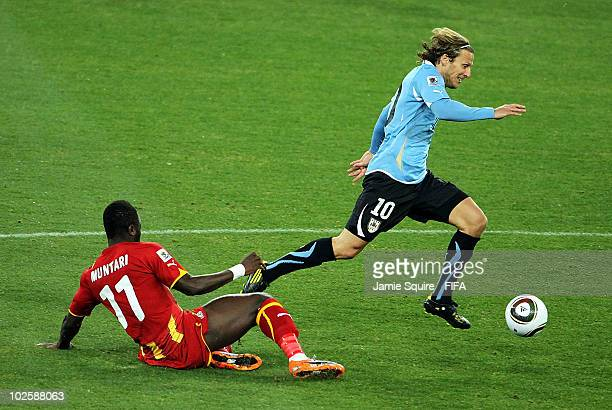Diego Forlan of Uruguay evades the tackle by Sulley Muntari of Ghana during the 2010 FIFA World Cup South Africa Quarter Final match between Uruguay...