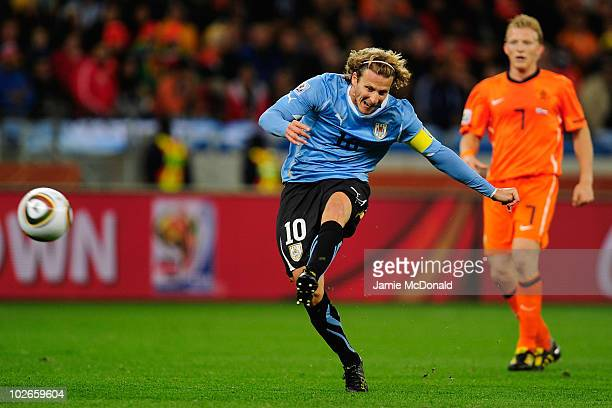 Diego Forlan of Uruguay shoots a long range effort and scores his team's first goal during the 2010 FIFA World Cup South Africa Semi Final match...