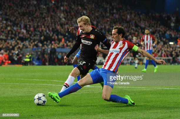 Diego Godin #2 of Atletico de Madrid and Julian Brandt #19 of Bayern Leverkusen compete during the UEFA Champions League Round of 16 second leg match...