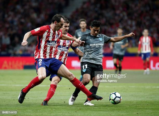 Diego Godin and Gabi of Atletico Madrid and Chory Castro of Malaga compete for the ball during Spanish La Liga match between Atletico Madrid and...